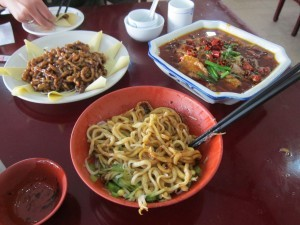 A selection of delicacies for lunch including some noodles, and boiled beef with peppers.