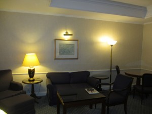 Another view of my suite's living room with armchair, sofa, coffee table and breakfast area.