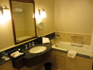 The bathroom of a standard room with separate tub/shower and a single sink.