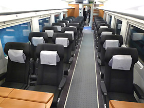The tourist class section of a RENFE train with the 4-person table at the front.