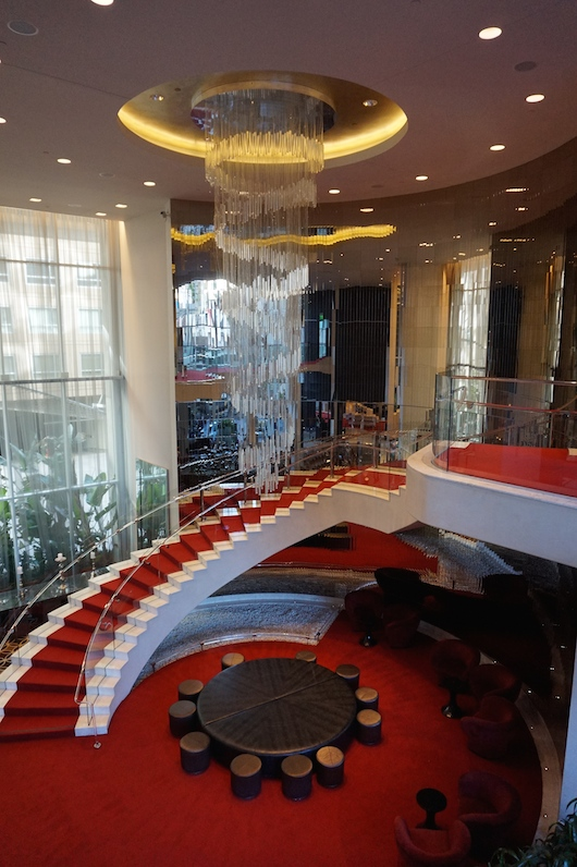 The dramatic red carpet staircase and chandelier in the lobby.