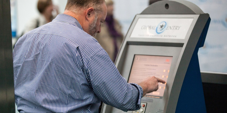 Man using a new Global Entry kiosk at Newark Liberty International Airport.