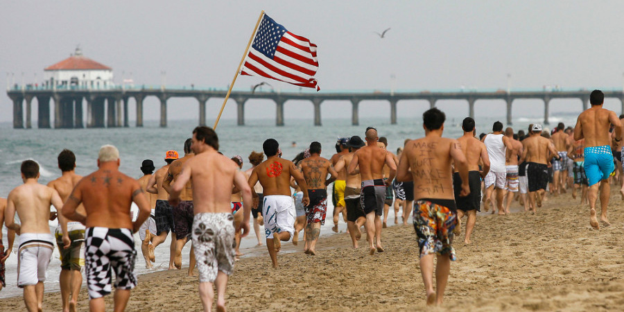 Participants run down the beach towards the Manhattan pier during the first leg of the Iron Man competition on Saturday, July 4, 2009 in Hermosa Beach, Calif. Competitors haul themselves, flags, and beer into the air to celebrate Independence Day and show their patriotism as part of the Iron Man competition. In the Iron Man, a Hermosa Beach 4th of July tradition for 32 years, participants must run a mile, paddle board a mile, then chug a six-pack of beer, awards are given to those who do not puke – and those who puke the best. © 2009 Patrick T. Fallon