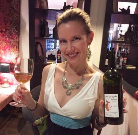 A friend of the author's sampling a glass of amber wine, something that is unique to Georgia.