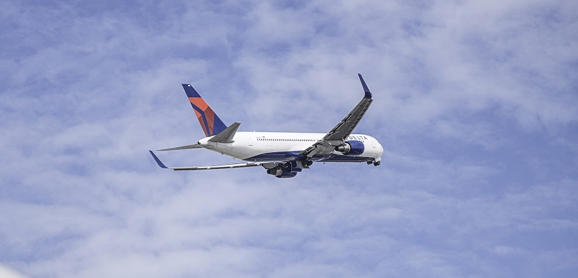 A Boeing 767-300ER (76T) departing over a Boeing 777-200ER (777) engine. - These images are protected by copyright. Delta has acquired permission from the copyright owner to the use the images for specified purposes and in some cases for a limited time. If you have been authorized by Delta to do so, you may use these images to promote Delta, but only as part of Delta-approved marketing and advertising. Further distribution (including proving these images to third parties), reproduction, display, or other use is strictly prohibited.